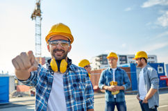 Builders pointing finger at you on construction. Business, building, teamwork and people concept - group of smiling builders in hardhats pointing finger at you royalty free stock photography