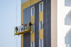Builders put on plaster on the walls of a high-rise modern build royalty free stock image
