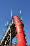 Builders Rubble Chute. Red builders rubble chute and scaffolding with blue sky Royalty Free Stock Photography