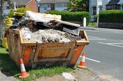 Builders Rubble Skip. Filled builders rubble skip on the roadside stock photo