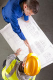Builders shake hands over blueprint Stock Images