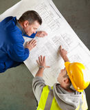 Builders share humor about blueprints Royalty Free Stock Photo