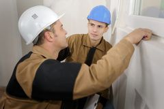 Builders sharing a joke. Window Royalty Free Stock Images