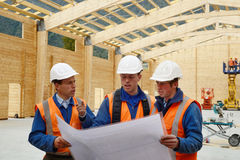Builders study the plan. Three builders discuss the plan for a major construction job Royalty Free Stock Image