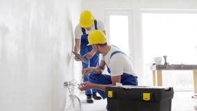 Builders with tablet pc and equipment indoors stock video