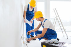 Builders with tablet pc and equipment indoors Royalty Free Stock Images