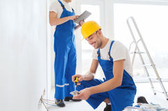 Builders with tablet pc and equipment indoors. Building, renovation, technology, electricity and people concept - two builders with tablet pc computer working Royalty Free Stock Image