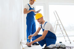 Builders with tablet pc and fixing wiring indoors Stock Photos