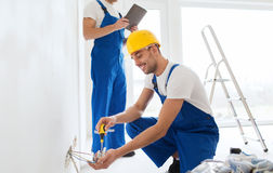 Builders with tablet pc and fixing wiring indoors. Building, renovation, technology, electricity and people concept - two builders with tablet pc computer fixing Royalty Free Stock Photos