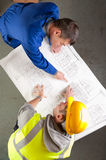 Builders talk about blueprint on bench Royalty Free Stock Photography