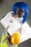 Builders talk about blueprint on bench Royalty Free Stock Photos