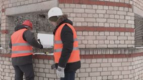 Builders talking near unfinished building. In winter day stock video footage