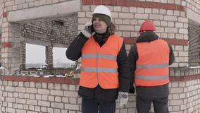 Builders talking on smart phone near unfinished building. In winter day stock video footage