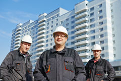 Builders team at construction site. Team of smiling foreman builders workers in protective uniform at construction building site stock photography