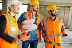 Builders. Three professionals in uniform and hardhats standing on construction site Royalty Free Stock Photo