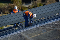 Builders on top. A builder screws down roofing iron for the roof on a large commercial building near Greymouth, New Zealand Royalty Free Stock Photo