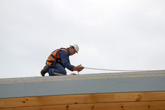 Builders on top. A builder secures safety lines for man about to put the roof on a large commercial building Royalty Free Stock Photography