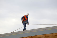 Builders on top. A builder secures safety lines for man about to put the roof on a large commercial building Stock Images
