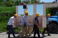 Builders transport the furniture frame to public shells!. Workers, men, build helmet, cobbles, diligently, diligence, effort, hard, together, team, brigade royalty free stock image