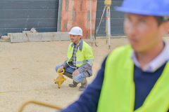 Builders using measuring tools outdoors in construction site Royalty Free Stock Image