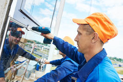 Builders worker installing glass windows on facade Royalty Free Stock Images