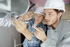 Builders working on house ventilation pipes. Builders royalty free stock image