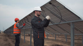 The builders working with wires. The builders connecting the solar energy panels with the wires Royalty Free Stock Photos