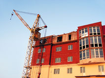 Building. The building crane stands near a builded house Royalty Free Stock Photos