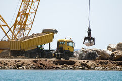 Building A Dike. Cranes And Excavator Put Stones Stock Image