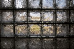 Building of an abandoned and destroyed farm is seen through a partially broken, dirty window of glass blocks in the village. royalty free stock image