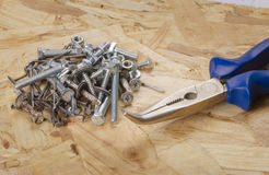 Building accessories. Pliers, bolts,screws, nails. On particleboard Stock Images