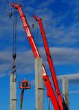 Building activity. Two telescopic cranes and a cherry pickers install the first concrete structural columns for a new construction Royalty Free Stock Photos