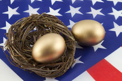 Building American Prosperity. Two, gold eggs, one in twig nest and one directly on American flag, depict the financial building of personal as well as national stock image