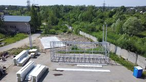 Building area with packed constructing materials and white metallic construction. Aerial view of big building area with packed long rectangular construct stock footage