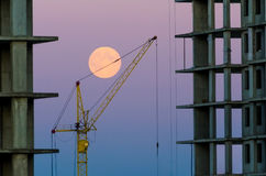 Building in the background a crane and evening sky with a full moon. Stock Photo