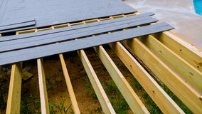 Building a backyard deck with composite deck boards. Installing wooden deck patio royalty free stock image