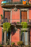 Building in Barcelona made of red bricks, outdoor view on balcony with flowers. Royalty Free Stock Photos