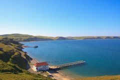 Building by a bay. Old Building with a pier by the water, Drakes Bay, Point Reyes NS, California Royalty Free Stock Image