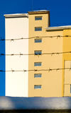 Building behind barbed wire. Building behind the barbed wire against the blue sky Stock Images