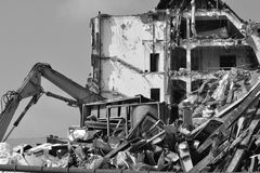 Demolition and bulldozer. A building being wrecked with a bulldozer detail in front in black and white Stock Photo