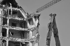 Demolition and bulldozer with crane. A building being wrecked with a bulldozer detail in front and a crane above in black and white stock photos