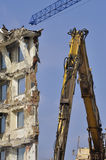 Demolition, crane and bulldozer. A building being wrecked with a bulldozer detail in front and a new crane above stock images