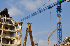 Demolition, cranes and bulldozer. A building being wrecked with a bulldozer detail in front and two new cranes royalty free stock images