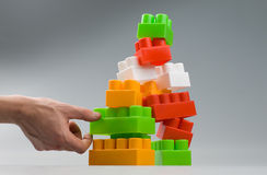 Building blocks. A tower of building blocks about to crumble Royalty Free Stock Photography