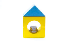 Building blocks with coins inside the hole. Stock Photo