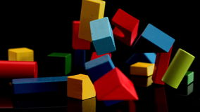 Building blocks falling and bouncing on black background stock footage