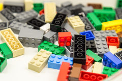 Building blocks with focus and highlight on one selected block with available light. A pile of building blocks with focus and lighting on one single block Royalty Free Stock Photo