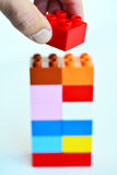 Building blocks. Mans hand puts a red toy block on top of a building blocks tower in the background. concept photo of imagination, creativity, planning and ideas stock photos