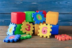Building blocks and puzzle pieces on background. Building blocks and puzzle pieces on wooden background stock images