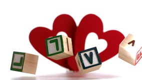 Building blocks spelling out love falling with heart ornament stock video footage